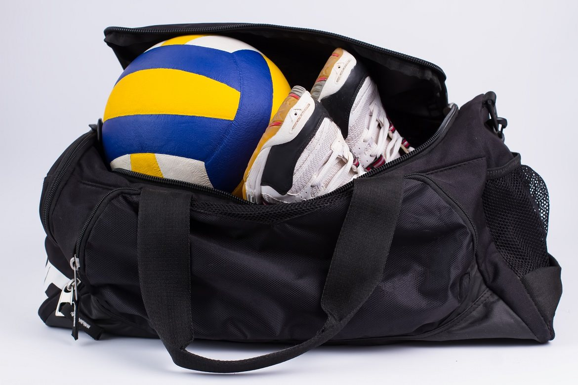 Sports bag with sports equipment on white background.