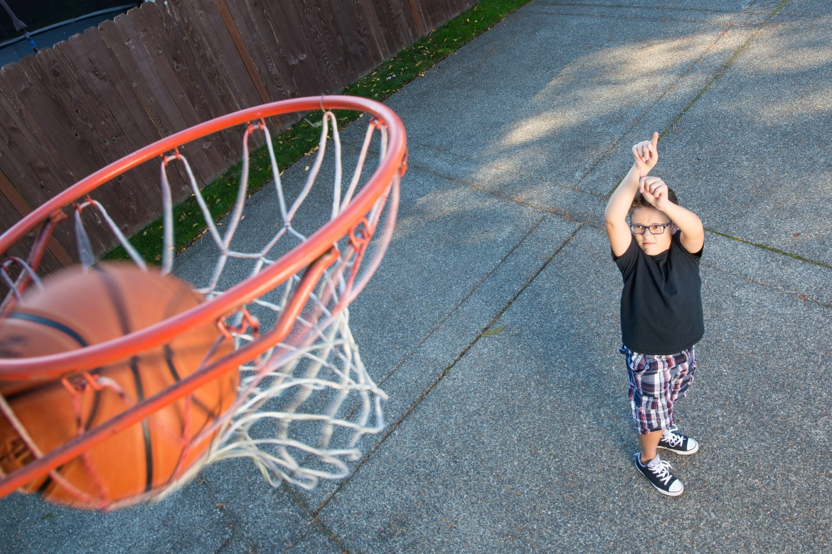 Young boy throwing a basketball in a net