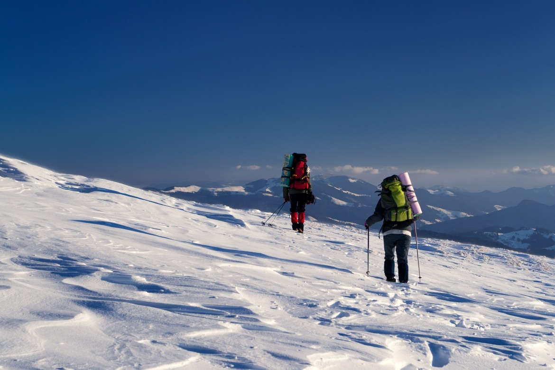 Na zdjęciu dwóch podróżników w górach. Wybrali nordic walking zimą jako sposób spacerowania.